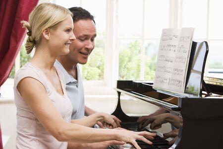 tocando piano: Joven tocando el piano y sonriente