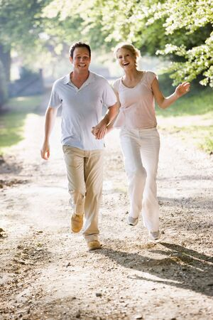 Couple running outdoors holding hands and smiling Stock Photo - 3603273