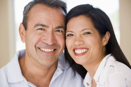 mixed age: Couple in living room smiling