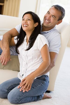 filipino people: Couple in living room laughing Stock Photo