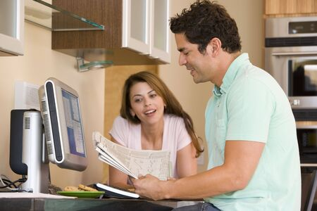 Couple in kitchen with computer and newspaper smiling photo
