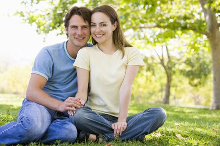 Couple sitting outdoors smiling photo
