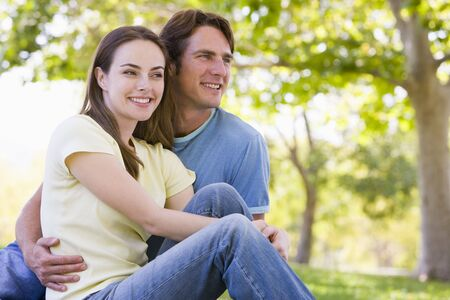 boy romantic: Couple sitting outdoors smiling