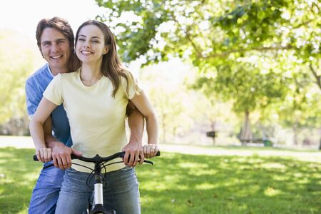 Couple on a bike outdoors smiling Stock Photo - 3603714
