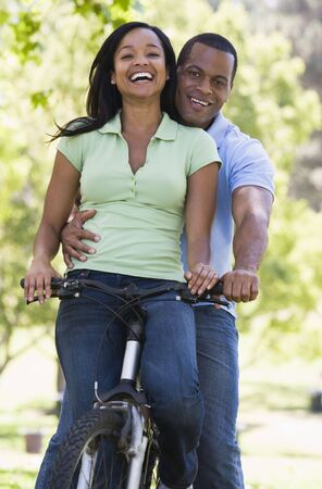 Couple on a bike outdoors smiling Stock Photo - 3602870