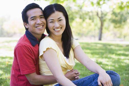 Couple sitting outdoors smiling photo