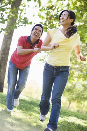 Couple running and being playful outdoors smiling photo