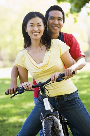happy asian couple: Couple on a bike outdoors smiling Stock Photo