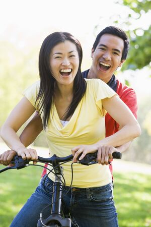 Couple on a bike outdoors smiling photo