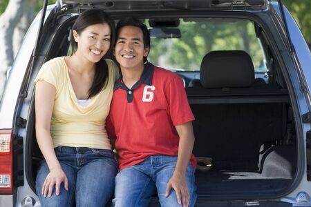 Couple sitting in back of van smiling Stock Photo - 3603486