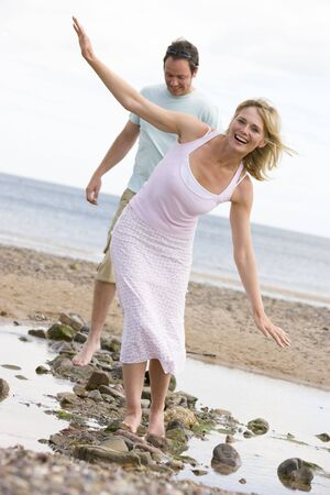 balancing: Couple at the beach walking on stones and smiling
