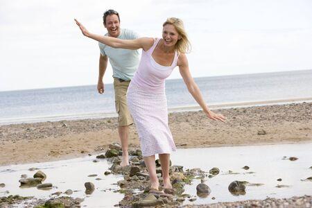 parejas caminando: Pareja en la playa caminando sobre las piedras y sonriente Foto de archivo