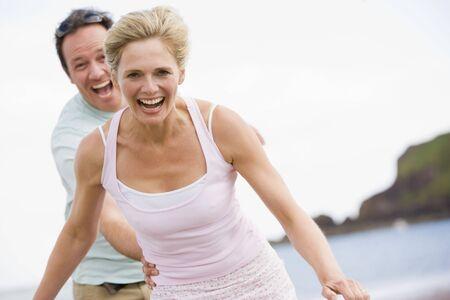 pareja saludable: Joven en la playa sonriente
