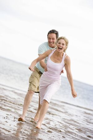 Couple running at the beach smiling photo
