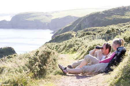 Couple on cliffside outdoors using binoculars and smiling photo