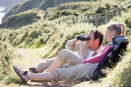 Couple on cliffside outdoors using binoculars and smiling Stock Photo - 3603485