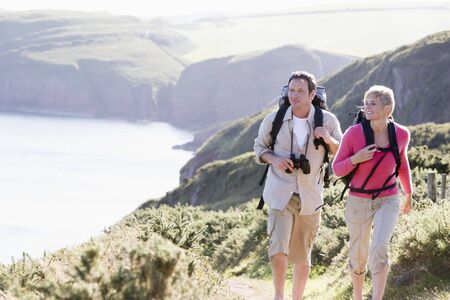 Couple on cliffside outdoors walking and smiling photo