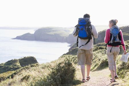 Couple on cliffside outdoors walking photo