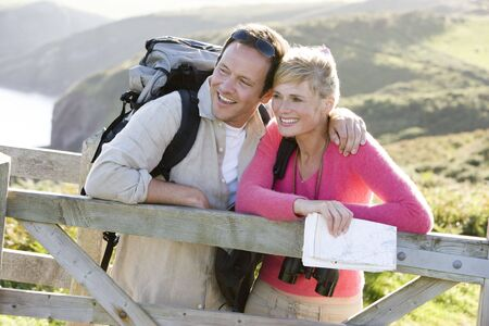 ruck sack: Couple on cliffside outdoors leaning on railing and smiling Stock Photo
