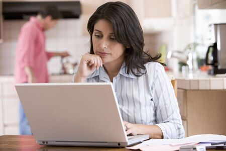 Woman in kitchen with paperwork using laptop with man in background photo