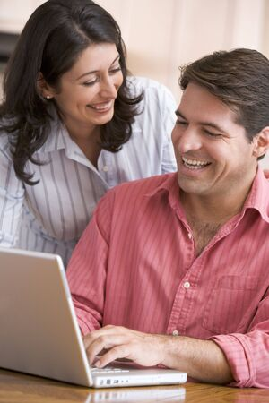 Couple in kitchen using laptop smiling photo