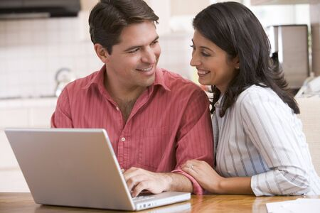 Couple in kitchen using laptop and smiling photo