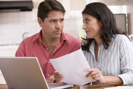 Couple in kitchen with paperwork using laptop looking unhappy photo