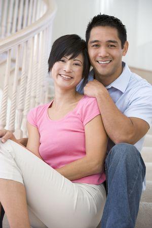 asian home: Coppia sorridente seduto su scala