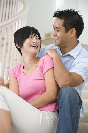 couple home: Couple sitting on staircase smiling Stock Photo