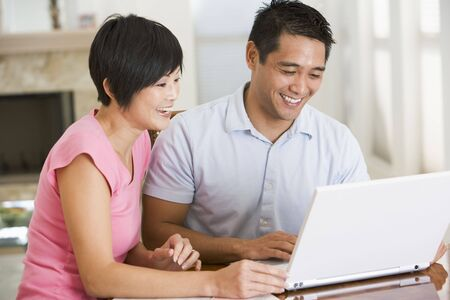 asian working woman: Couple in dining room with laptop smiling