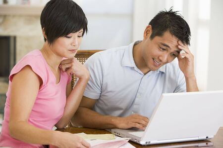 Couple in dining room with laptop looking unhappy photo