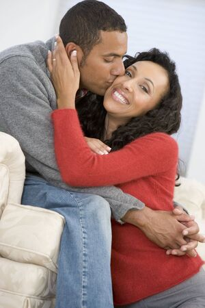 Couple in living room kissing and smiling photo
