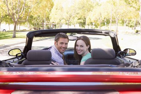 early thirties: Couple in convertible car smiling Stock Photo