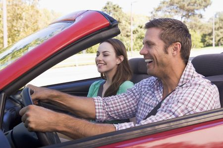 generation x: Couple in convertible car smiling Stock Photo