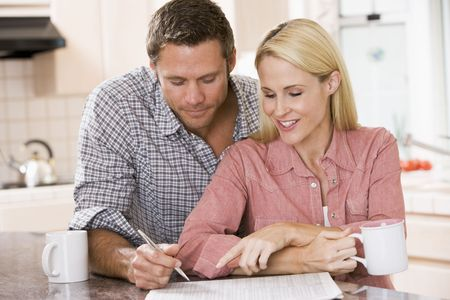 Couple in kitchen with newspaper and coffee smiling photo