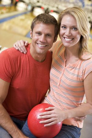 Couple in bowling alley holding ball and smiling photo
