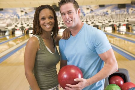 bowling alley: Couple in bowling alley holding ball and smiling