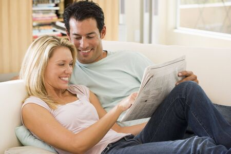 Couple in living room reading newspaper and smiling photo