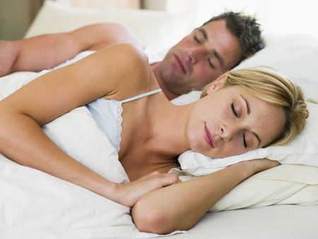 Couple lying in bed sleeping Stock Photo