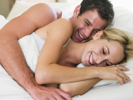 sexy woman on bed: Couple lying in bed laughing Stock Photo