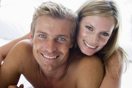 Couple lying in bed smiling photo