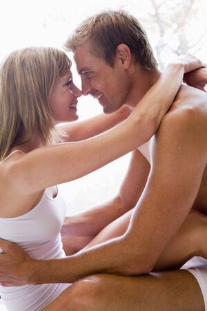 Couple in bedroom embracing and smiling photo