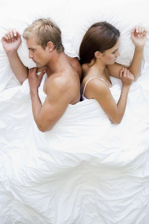 relationship problems: Couple lying in bed back to back looking unhappy Stock Photo
