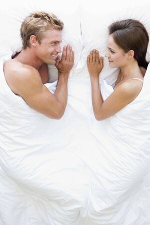 wake up happy: Couple lying in bed smiling
