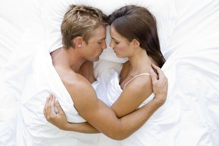 personas abrazadas: Pareja en la cama para dormir Foto de archivo