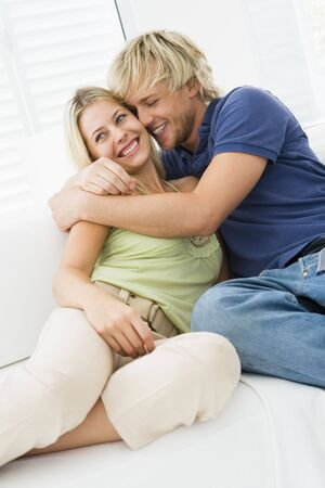 Couple in living room hugging and smiling photo