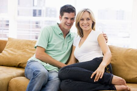younger man: Couple in living room smiling