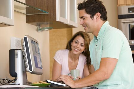 Couple in kitchen with computer and coffee smiling Stock Photo - 3602746