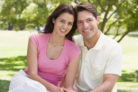 relationship love: Couple sitting outdoors smiling