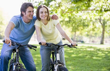 Couple on bikes outdoors smiling photo